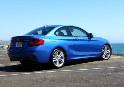 A three-quarter rear view of a 2015 BMW 228i Coupe