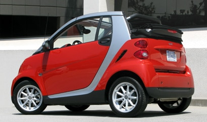 A three-quarter rear view of a red and silver 2008 smart fortwo passion cabriolet