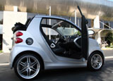 A side view of a silver 2009 smart fortwo brabus cabriolet