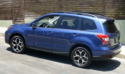 A three-quarter rear view of a blue Subaru Forester
