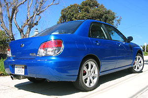 A three-quarter rear view of a blue 2006 Subaru Impreza WRX TR