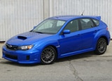 A three-quarter front view of a blue 2012 Subaru Impreza WRX 5-Door