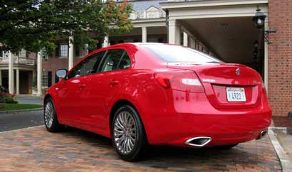 A three-quarter rear view of a red 2010 Suzuki Kizashi