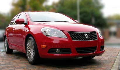 A three-quarter front view of a red 2010 Suzuki Kizashi