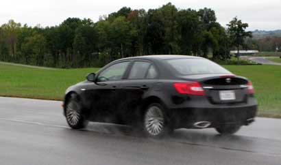 A black 2010 Suzuki Kizashi speeding down the track at the VIRginia International Raceway