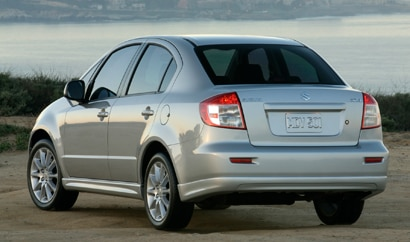 A three-quarter rear view of a silver 2011 Suzuki SX4 sedan