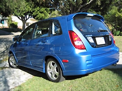 A three-quarter rear view of a blue 2004 Suzuki Aerio SX