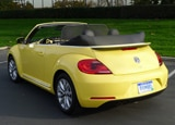 A three-quarter rear view of a yellow 2013 Volkswagen Beetle TDI Convertible