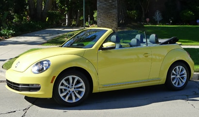 A three-quarter front view of a yellow 2013 Volkswagen Beetle TDI Convertible