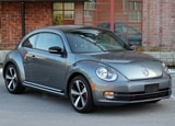 A three-quarter front view of a silver 2012 Volkswagen Beetle Turbo