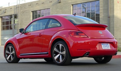A three-quarter rear view of a red 2012 Volkswagen Beetle Turbo
