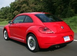 A three-quarter rear view of a red 2011 Volkswagen Beetle