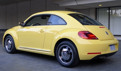 A three-quarter rear view of a yellow 2012 Volkswagen Beetle