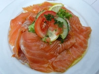 A plate of smoked salmon with tomatoes and cucumbers