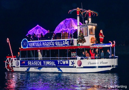 "Event-goers wave from one of the ""Dreamer"" vessels at the California Sleigh Rides event in Ventura Harbor, CA"