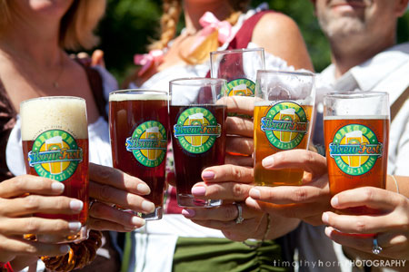 Attendees hold up mixed craft beers for a cheers at the Oregon Brewers Festival in Portland