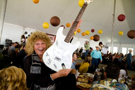A woman wins a signed guitar during the auction at Harvest on the Coast in San Luis Obispo, CA
