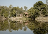 A view of the dining hall from across the lake at Shergarh Tented Camp