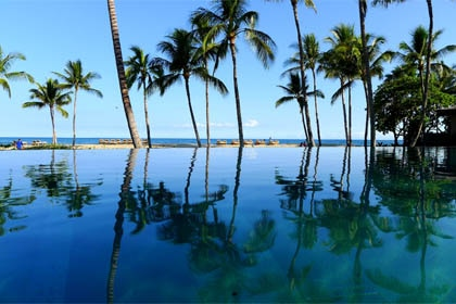 The adult-only, infinity-edge Palm Grove Pool at Four Seasons Hualalai at Historic Kaupulehu in Hawaii