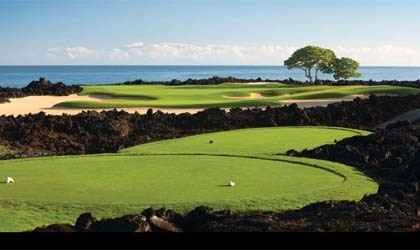 The golf course at Four Seasons Resort Hualalai at Historic Ka'upulehu meanders along black lava contours, showcasing sweeping ocean views