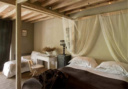 A shabby chic guest room at Conti Di San Bonifacio Wine Resort in Tuscany, one of GAYOT's Top 10 Hotels in Italy