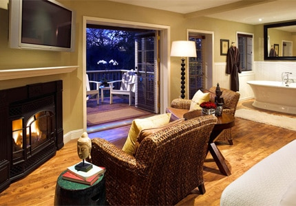 A guest room with a fireplace and private deck at Milliken Creek Inn, one of GAYOT'S Top 10 Romantic Hotels in Napa/Sonoma, CA
