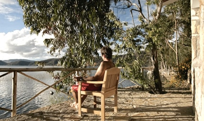 A guest sits outside Casa Andina Private Collection Isla Suasi in Peru