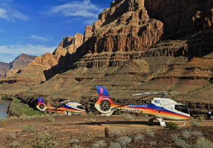 A Papillon Airways helicopter surrounded by the imposing walls of the Grand Canyon