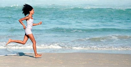 A woman runs on the beach at Canyon Ranch Miami Beach in Florida
