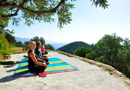 Guests participating in stretching at Silver Island Yoga in Greece, which is included in GAYOT.com's list of Top 10 Yoga Retreats