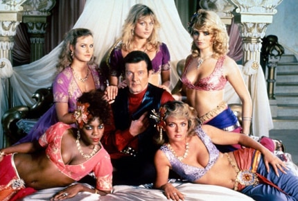 Roger Moore surrounded by beautiful women in Octopussy