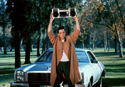 John Cusack in the classic boombox scene from Say Anything, included in GAYOT's list of Top Romantic Comedies