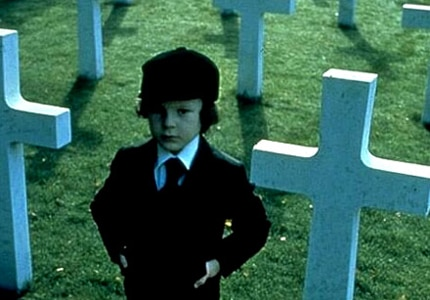 An orphaned child has a dark secret in The Omen, one of GAYOT's Top 10 Scary Movies