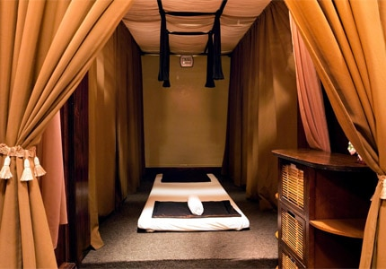 Guests lie on comfortable, ultra-low cots for massages at Pho Siam Thai Spa