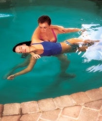 A woman receives a Watsu massage in their body-temperature shallow pool