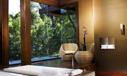 A bath area with floor-to-ceiling windows at the Gwinganna Lifestyle Retreat spa in Queensland, Australia