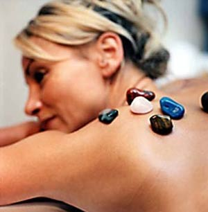 A woman receives the Healing Stone Therapy treatment, the signature selection at the New Age Health Spa