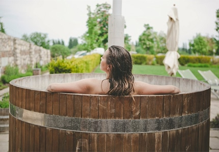 A woman relaxing in a barrel bath at the spa in Crocus Gere Bor Hotel, Hungary