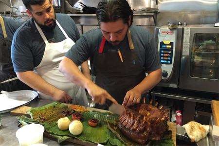 Chef Ray Garcia carving out a rack of heritage pork in preparation for Cochon 555