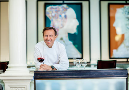 Daniel Boulud enjoying a glass of wine at Daniel(photo by Thomas Schauer)