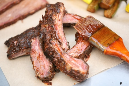 A 1,700-pound smoker cooks up pork back ribs at Charcoal BBQ, one of GAYOT's Top 10 Barbecue Restaurants in Los Angeles