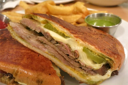 Chef David Kuo's Mar Vista restaurant, Status Kuo, presents a menu of rotisserie meats and sandwiches, including a Cubano