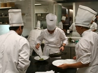 A group of chefs plating a dish