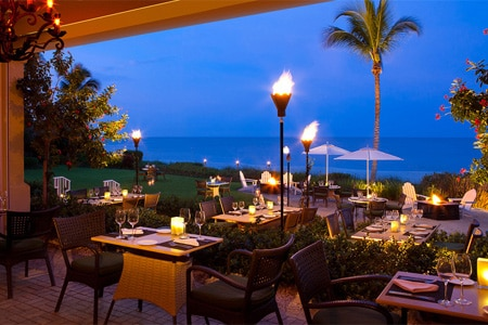 Indoor-outdoor seating overlooks a swath of beach and Gulf of Mexico at Naples' most elegant hotel restaurant.