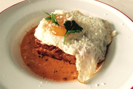 Trois Familia's chilaquiles are a crisp square of delicate hash browns topped with a sunny side up egg, cotija cheese and fresh salsa