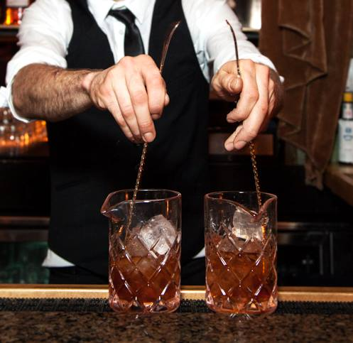 A waiter stirs a handcrafted rum drink