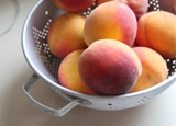 Fresh peaches in a colander