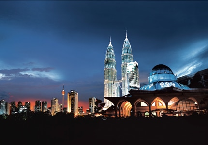 The Petronas Towers dominate the nighttime skyline of Kuala Lumpur