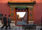 Two men walk past an entryway in Beijing