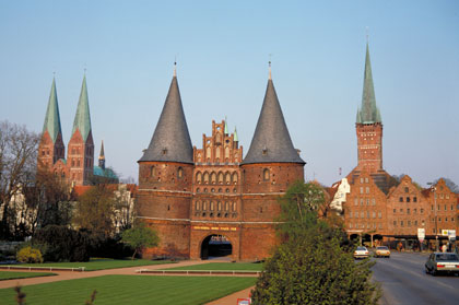 The massive Holstentor, symbol of Lübeck, along with St. Marien and St. Petri Church in Germany